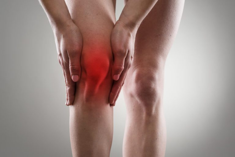Person grabbing knee in pain from Knee Osteoarthritis